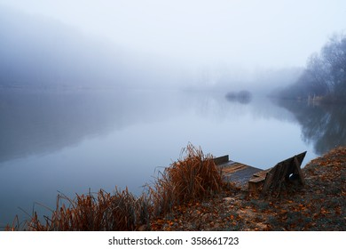 Pier on winter foggy lake