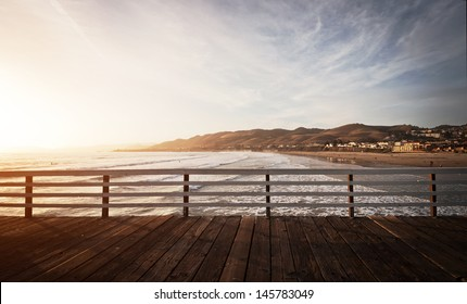 The pier in Pismo Beach, California is silhouetted by a beautiful orange sunset.