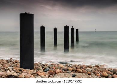Pier posts in the ocean on stormy day. Viken, Sweden.