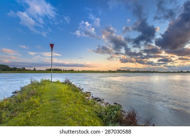 Pier preventing erosion in the river Rhine with bright blue skay and beautiful cloudscape during sunset