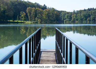 A pier with a railing on the pond in Konopiste