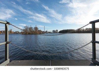 Pier at River - Chain Fencing Close Up - Under a Blue Cloudy Sky - Industry in the Background