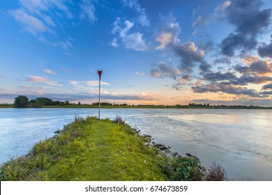 Pier in the river Rhine with bright blue skay and beautiful cloudscape during sunset