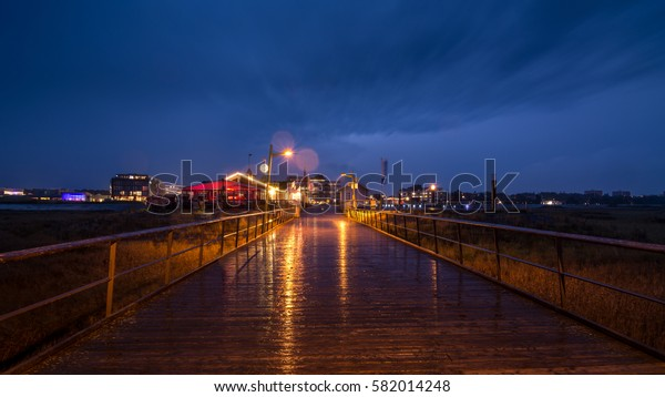 Pier of Sankt Peter Ording Bad under a thunder storm at dusk, North Sea in Germany