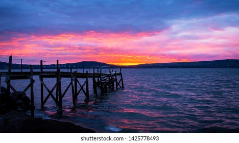 Pier and sea under beautiful sunset from long exposure at the Holywood harbour, Northern Ireland.