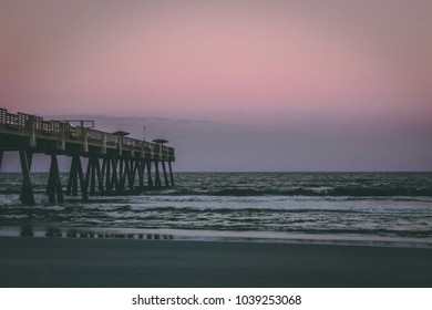 Pier at the sea with waves and a beautiful pink sunset