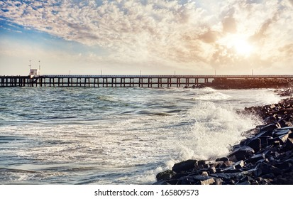 Pier and sea with waves at sunset sky background in Puducherry, India