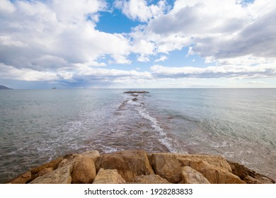 A pier of stones, a pier going into the sea. Dramatic sky with dark, heavy clouds. Copy space