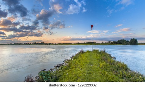 Pier  or strekdam in the river Rhine with bright blue skay and beautiful cloudscape during sunset