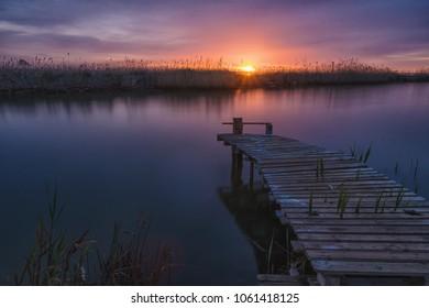 Pier at sunrise in Delta del Ebro natural Park, Tarragona, Catalunya, Spain