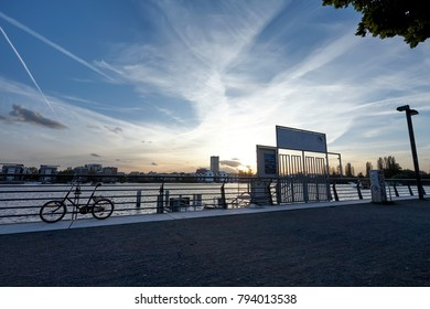 Pier at Sunset on a River, under a Blue Cloudy Sky, with a Bike nearby and a Cityscape in the Background