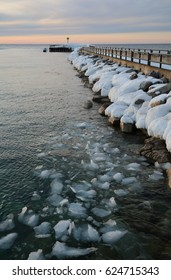 A pier at sunset in the winter with snow covered rocks and chunks of ice in the water in the foreground.