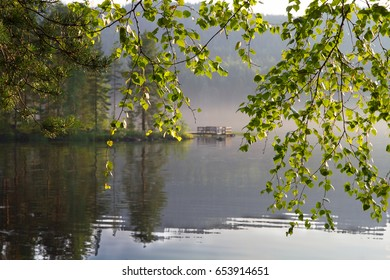 Pier through the branches of trees. Sunrise in finnish lake in a summer day.