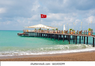 A pier with a Turkish flag on the beach in Side. Turkey