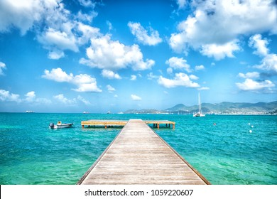 Pier in turquoise sea and blue sky with white clouds in philipsburg, sint maarten. Freedom, perspective and future. Beach vacation at Caribbean, wanderlust.