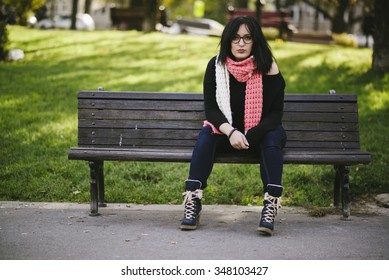 pierced girl posing and  on park bench