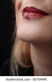 Pierced red lips of young adult caucasian female woman against a dark background.