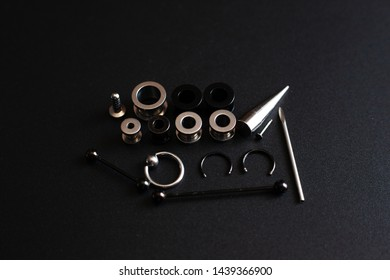 piercing accessories on a black background close-up stainless metal jewelry for puncture lovers