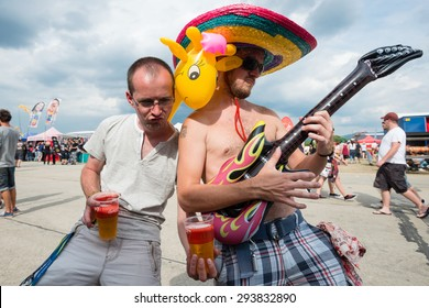 PIESTANY, SLOVAKIA - JUNE 27: Visitors of Slovak music festival Topfest having fun while playing on inflatable guitar in Piestany, Slovakia on June 27, 2015