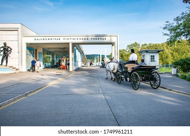 """PIESTANY, SLOVAKIA – MAY 16 2017:  Horse drawn carriage with driver and passengers in front of bridge to Spa island in Piestany. Text translation: """"Healing Piestany Spa"""""""
