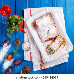 Pie,Strudel with Berries and Fruit.Baking with plums with fresh mint on a blue Background.selective focus.