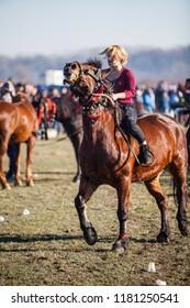 Pietrosani, Romania - January 6, 2018: Young woman riding a horse on Epiphany day celebrations in Pietrosani, Romania.