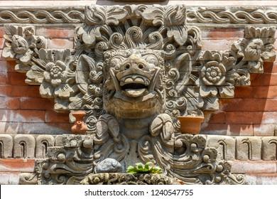 Pig head stone carving on Bale kul-kul or Balinese drum pavilion at Balinese Hindu temple Pura Dalem Suka Luwih, Batuan village, Kabupaten Gianyar, Bali, Indonesia