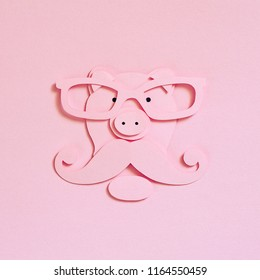 Pig Hipster cut from paper on a pink textured background, top view. Glasses, mustache and beard. Flat lay