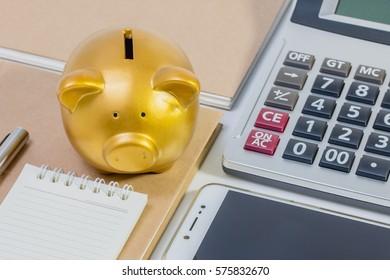 Pig piggy bank, calculator, phone, notebook, pen, concept of saving money