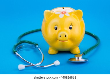 Pig piggy bank and stethoscope on a blue background.