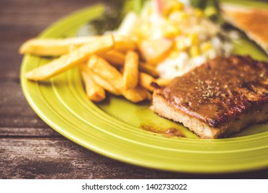 Pig steak is a fast food,pig steak this dish consists of with salad which has  purple lettuce corn apple cabbage salad dressing bread french fries and black pepper sauce, all in a green plate.