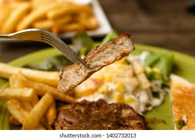 Pig steak use a fork to dip the meat,pig steak this dish consists of with salad which has  purple lettuce corn apple cabbage salad dressing bread french fries and black pepper sauce, in a green plate.