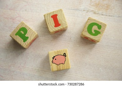 Pig Word Written in wooden cube. White wooden table. Soft daylight