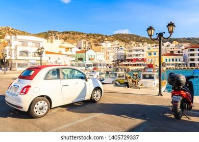 PIGADIA PORT, KARPATHOS ISLAND - SEP 26, 2018: Stylish Fiat 500 parking in picturesque Pigadia port on Karpathos island at sunset time, Greece.