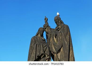 Pigeon sitting on sculpture's head on Charles Bridge, Prague, Czech Republic