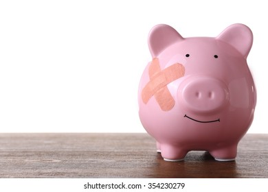 Piggy Bank with adhesive bandage wooden table, on white background