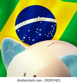Piggy bank against digitally generated brazilian national flag