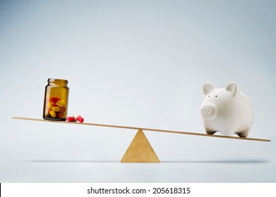 Piggy bank balancing on seesaw over a bottle of pills