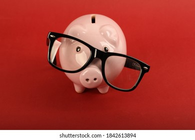 Piggy bank with black falling glasses on red background