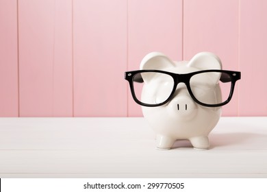 Piggy bank with black glasses on pink wooden wall
