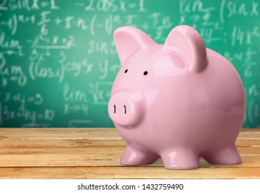Piggy Bank with Black Graduation Hat on blackboard background