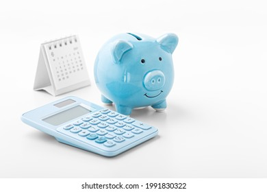 Piggy bank with blue calculator and calendar on white background, fiancial goal, money saving concept with copy space