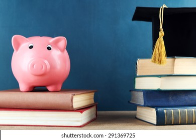 Piggy bank with books and Grad hat on blackboard background