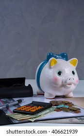 Piggy bank and business  assesories, glasses, calculator on white background