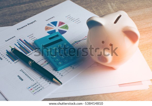 Piggy bank with business stuff, business and finance concept, vintage color tone.