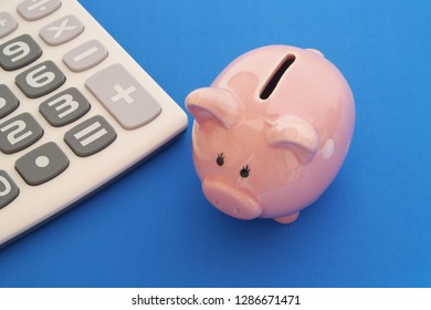 Piggy bank and calculator on blue background, save money concept