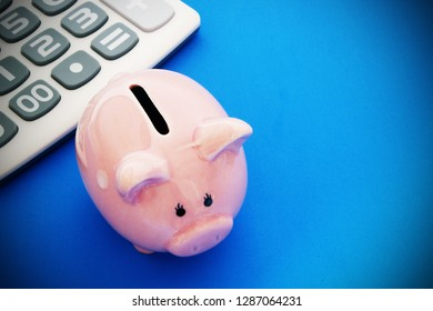 Piggy bank and calculator on blue background with space for text