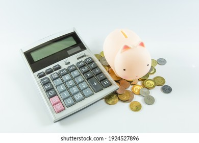 Piggy Bank and calculator on white background