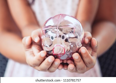 Piggy bank in child kid and mother hands. Family, saving,  investments concept