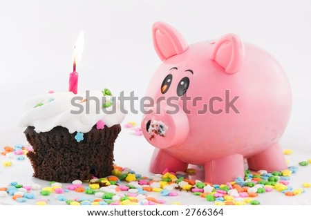 Piggy bank closely eyes cupcake with lit candle - sprinkles on plate beneath and white background behind